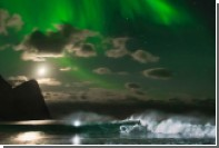 Серфингист прокатился по волнам при свете северного сияния